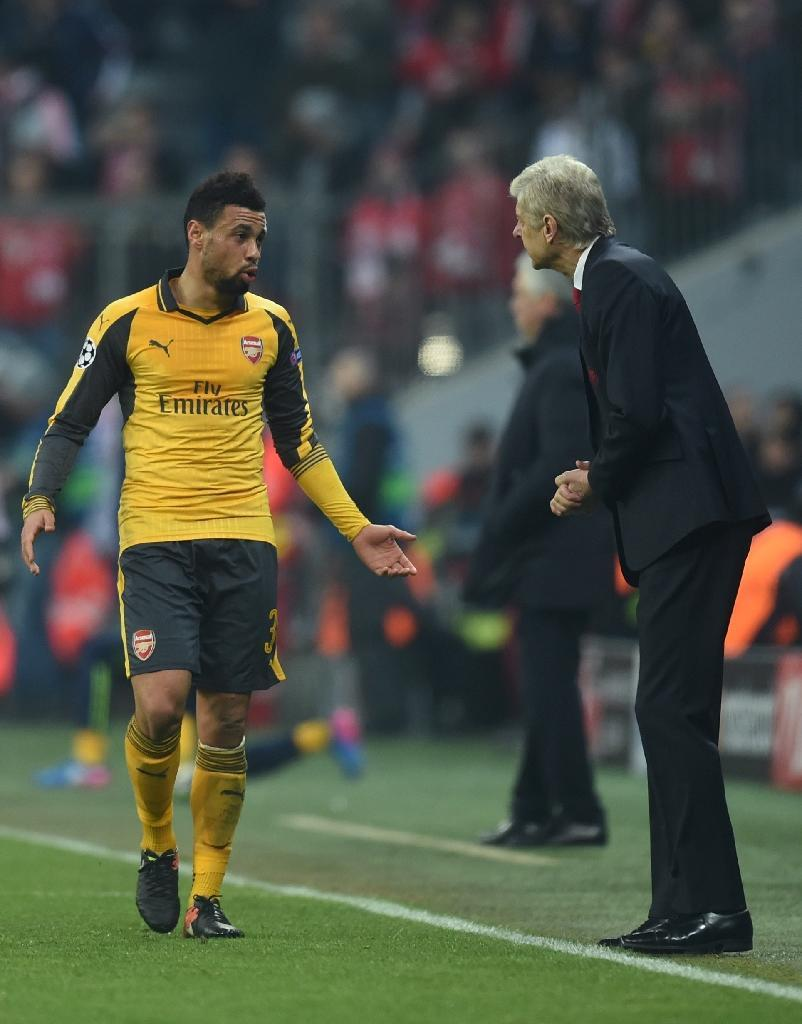 Arsenal's French midfielder Francis Coquelin (L) and head coach Arsene Wenger speak together during the Champions League round of 16 match against FC Bayern Munich in Munich, southern Germany, on February 15, 2017 (AFP Photo/Christof STACHE)
