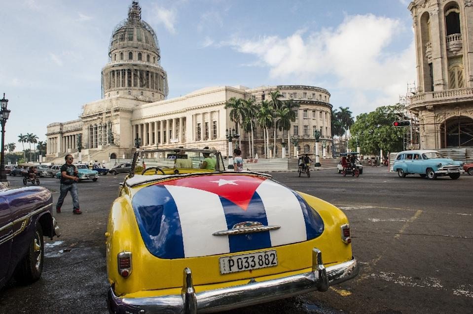 An old car with the Cuban flag painted on the trunk is seen near the Capitol of Havana, on January 7, 2015 (AFP Photo/Yamil Lage)