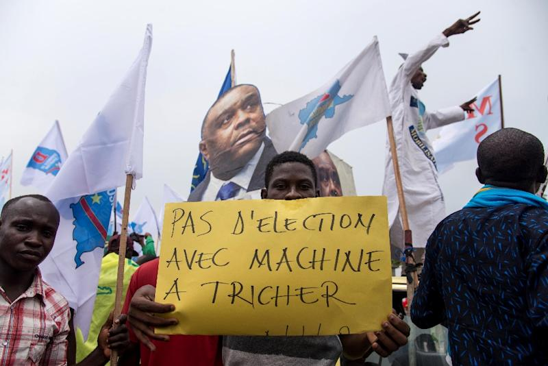 """An opposition supporter holds a sign reading """"No election with a cheating machine"""" -- there have been concerns about the use of electronic voting machines in DRC's poll (AFP Photo/Junior D. KANNAH)"""
