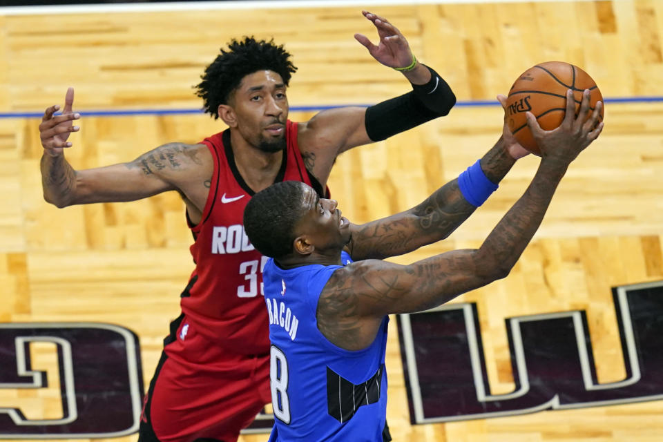 Orlando Magic guard Dwayne Bacon (8) goes past Houston Rockets center Christian Wood for a shot during the second half of an NBA basketball game, Sunday, April 18, 2021, in Orlando, Fla. (AP Photo/John Raoux)