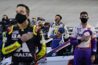 Alex Bowman, left, Chase Elliott, center, and Denny Hamlin listen to the national anthem before the NASCAR Cup Series auto race Saturday, Sept. 19, 2020, in Bristol, Tenn. (AP Photo/Steve Helber)