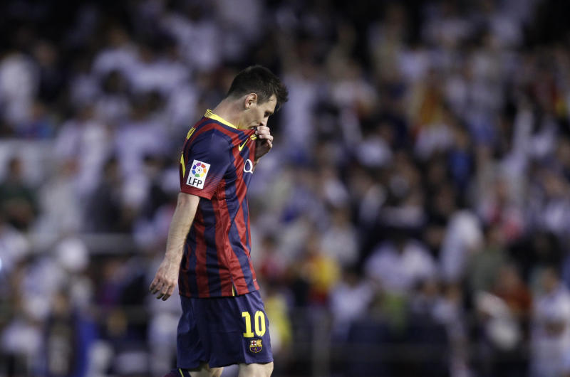 Barcelona's Lionel Messi touches his shirt during the final of the Copa del Rey between FC Barcelona and Real Madrid at the Mestalla stadium in Valencia, Spain, Wednesday, April 16, 2014. (AP Photo/Alberto Saiz)