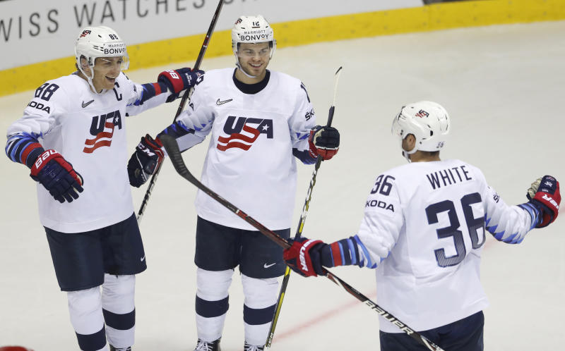 Alex Debrincat of the US, center, celebrates with teammates Patrick Kane, left, and Colin White, right, after scoring his sides fifth goal during the Ice Hockey World Championships group A match between Denmark and the United States at the Steel Arena in Kosice, Slovakia, Saturday, May 18, 2019. (AP Photo/Petr David Josek)