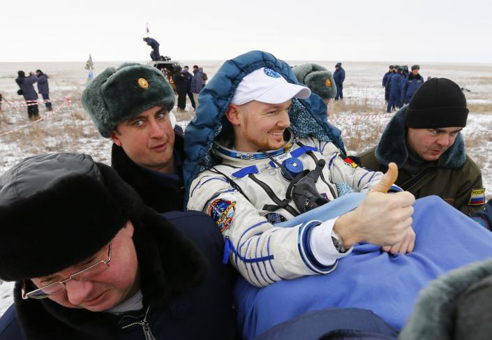 REFILE - CLARIFYING DATE OF LANDING IN SECOND SENTENCE Ground personnel carry International Space Station (ISS) crew member Alexander Gerst of Germany shortly after landing near the town of Arkalyk in northern Kazakhstan November 10, 2014. Veteran Russian cosmonaut Maxim Suraev and two International Space Station crewmates, NASA's Reid Wiseman from the United States and Gerst from Germany, returned safely to Earth on Monday with a parachute landing of their Soyuz capsule in Kazakhstan, ending 5-1/2 months in orbit. REUTERS/Shamil Zhumatov (KAZAKHSTAN - Tags: SCIENCE TECHNOLOGY)