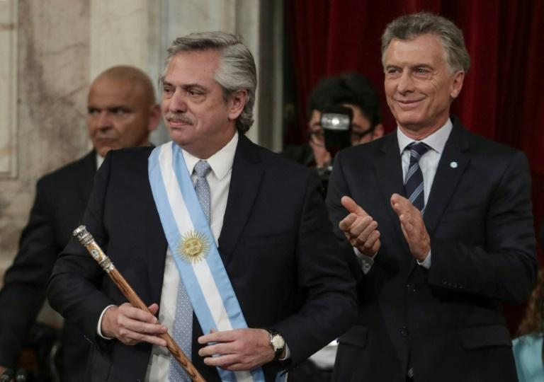 Alberto Fernandez dons Argentina's presidential sash after taking the oath of office, with outgoing president Mauricio Macri (R) by his side