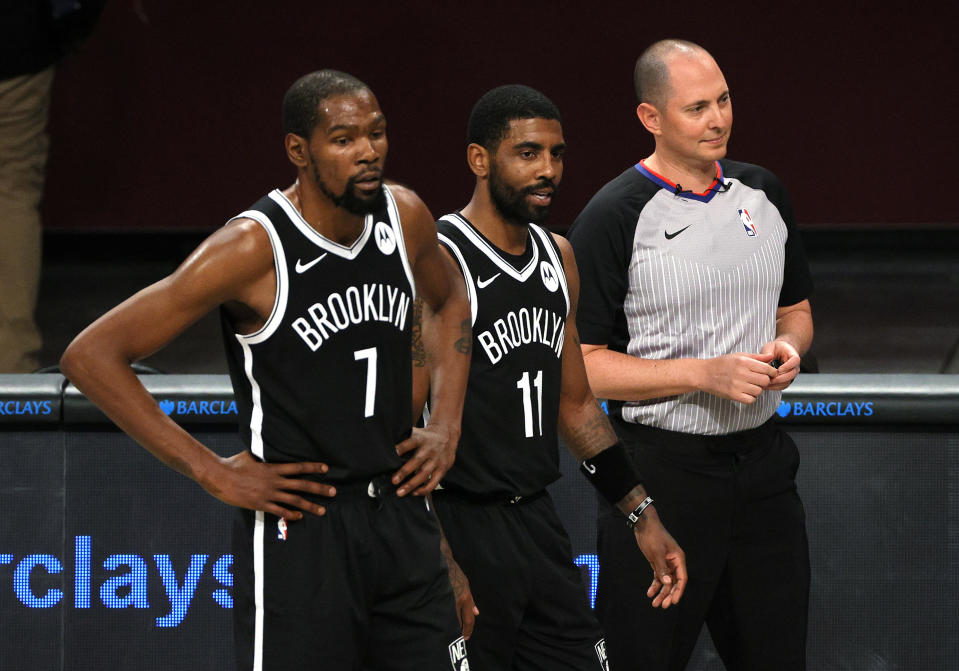 NEW YORK, NEW YORK - DECEMBER 13: Kevin Durant #7 and Kyrie Irving #11 of the Brooklyn Nets look on with the referee during the first half against the Washington Wizards at Barclays Center on December 13, 2020 in the Brooklyn borough of New York City. NOTE TO USER: User expressly acknowledges and agrees that, by downloading and or using this photograph, User is consenting to the terms and conditions of the Getty Images License Agreement. (Photo by Sarah Stier/Getty Images)