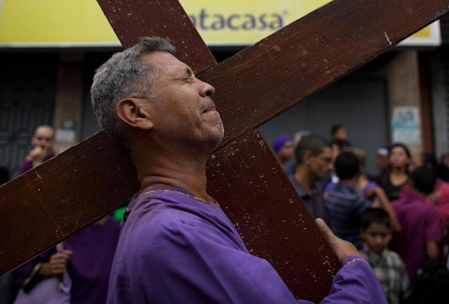 "<p>A man carries a cross during the procession of the ""Nazareno de San Pablo"" outside Santa Teresa Cathedral during Holy Week in Caracas, Venezuela, Wednesday, March 28, 2018. (Photo: Ariana Cubillos/AP) </p>"