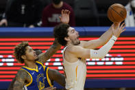 Cleveland Cavaliers forward Cedi Osman, right, shoots in front of Golden State Warriors guard Kelly Oubre Jr. during the second half of an NBA basketball game in San Francisco, Monday, Feb. 15, 2021. (AP Photo/Jeff Chiu)