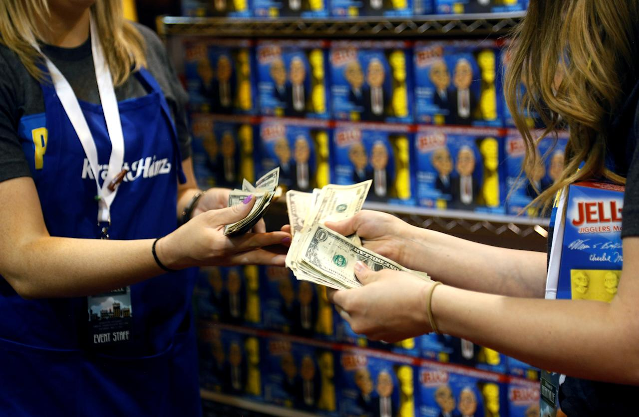 FILE PHOTO: Workers at the Kraft Heinz booth count money at the shareholder shopping day as part of the Berkshire Hathaway annual meeting weekend in Omaha, Nebraska, May 5, 2017. REUTERS/Rick Wilking/File Photo