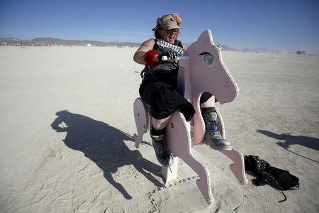 """Kentucky Sunshine, her Playa name, rides a rocking horse art installation during the Burning Man 2015 """"Carnival of Mirrors"""" arts and music festival in the Black Rock Desert of Nevada, September 1, 2015. REUTERS/Jim Urquhart"""