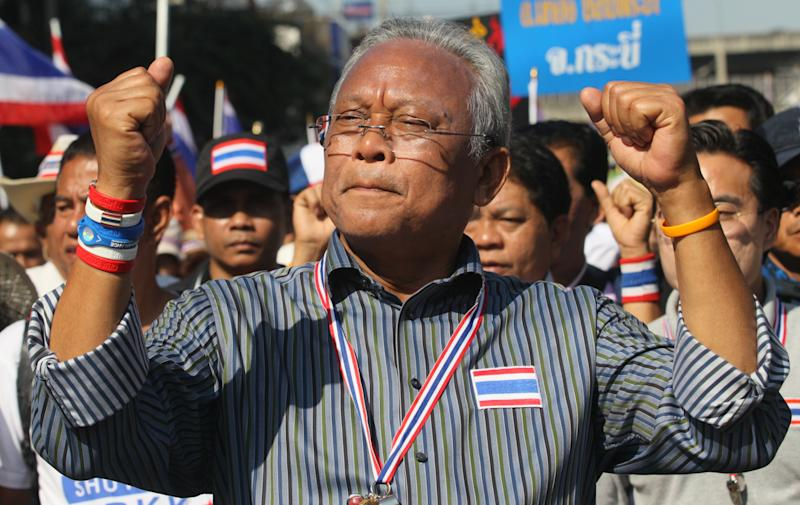 Thai anti-government protest leader Suthep Thaugsuban raises clenched fists during a march with his supporters in Bangkok, Thailand Monday, Jan. 13, 2014. Anti-government protesters took over key intersections in Thailand's capital Monday, halting much of the traffic into Bangkok's central business district as part of a months-long campaign to thwart elections and overthrow the democratically elected prime minister. (AP Photo/Sakchai Lalit)