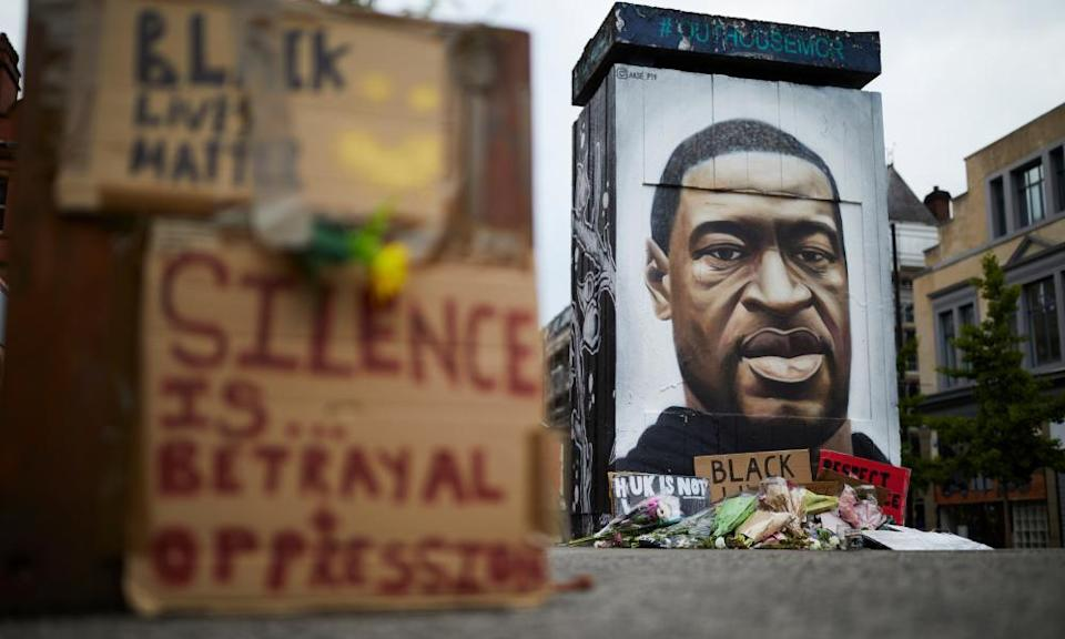 Flowers and tributes surround street artist Akse's mural of George Floyd in Stevenson Square, Manchester, UK.