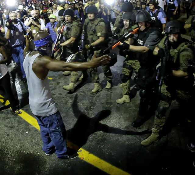 <p>Police arrest a man as they disperse a protest in Ferguson, Mo., early Wednesday, Aug. 20, 2014. On Saturday, Aug. 9, a white police officer fatally shot unarmed 18-year-old Michael Brown, who was black, in the St. Louis suburb. (AP Photo/Charlie Riedel) </p>