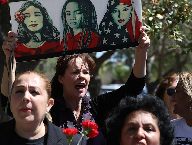 Laurie Woodward Garcia, center, joins other women on International Women's Day in front ofa U.S. Department of Homeland Security and Immigration and Customs Enforcement office to ask for fair treatment and dignity for women who are called to the office.