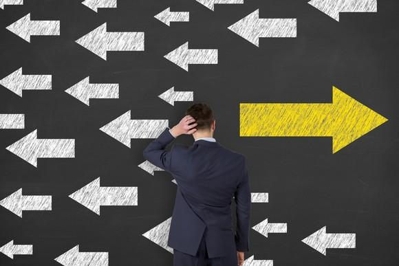 A businessman staring at a wall with many arrows pointing in one direction and one arrow pointing in the opposite direction.