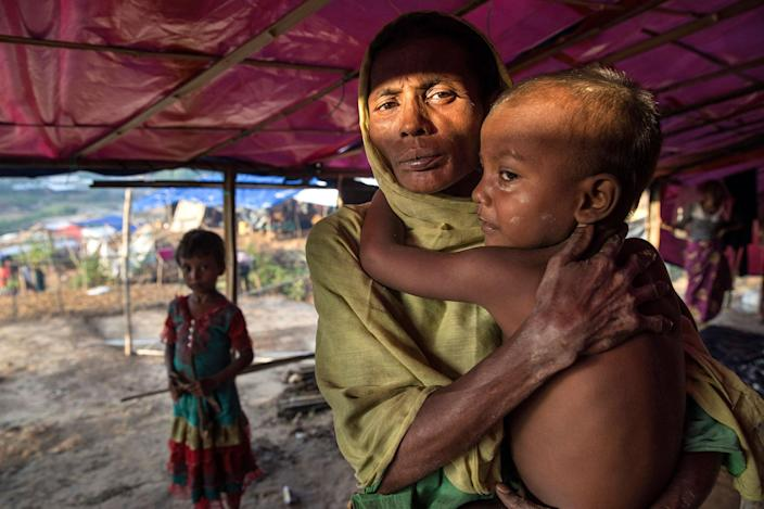 <p>Fleeing violence in Myanmar, Rohingya families arrive at Kutupalong. A Rohingya woman holds a young child in her makeshift tent at Kutupalong camp in Bangladesh on September 20, 2017. (Photograph by Paula Bronstein/UNHCR) </p>