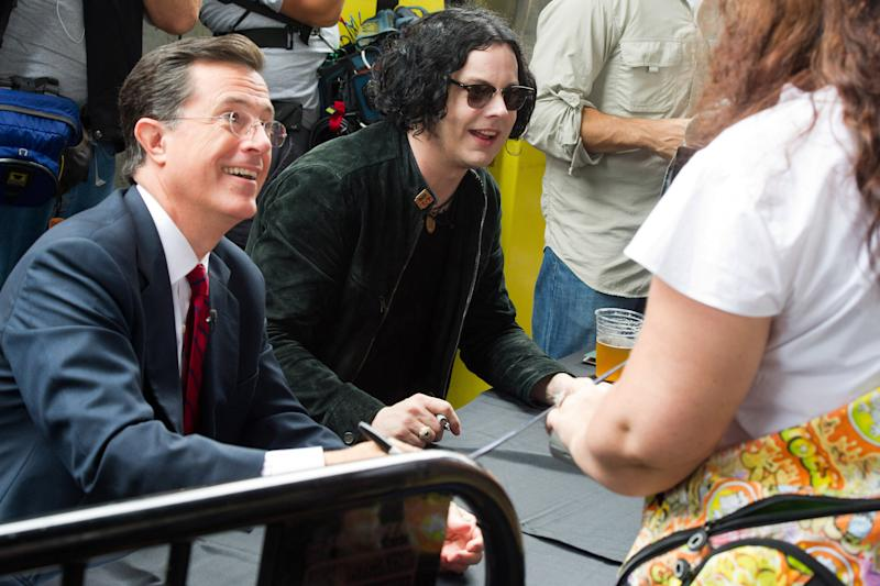 "Stephen Colbert, left, and Jack White sign copies of their vinyl record, ""Charlene II (I'm Over You),""  in New York, Friday, June 24, 2011. Colbert debuted his new Jack White-produced single on ""The Colbert Report"" on Thursday night. (AP Photo/Charles Sykes)"