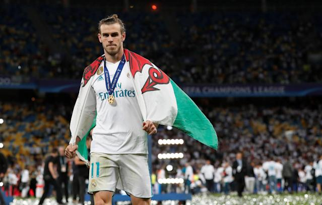 Soccer Football - Champions League Final - Real Madrid v Liverpool - NSC Olympic Stadium, Kiev, Ukraine - May 26, 2018 Real Madrid's Gareth Bale celebrates with a Wales flag after winning the Champions League REUTERS/Andrew Boyers