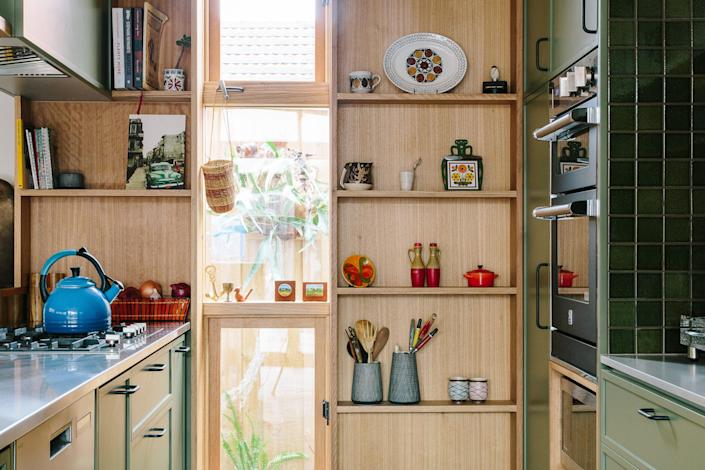 AFTER: Open shelving was built into the wall of the kitchen to maximize space and functionality.