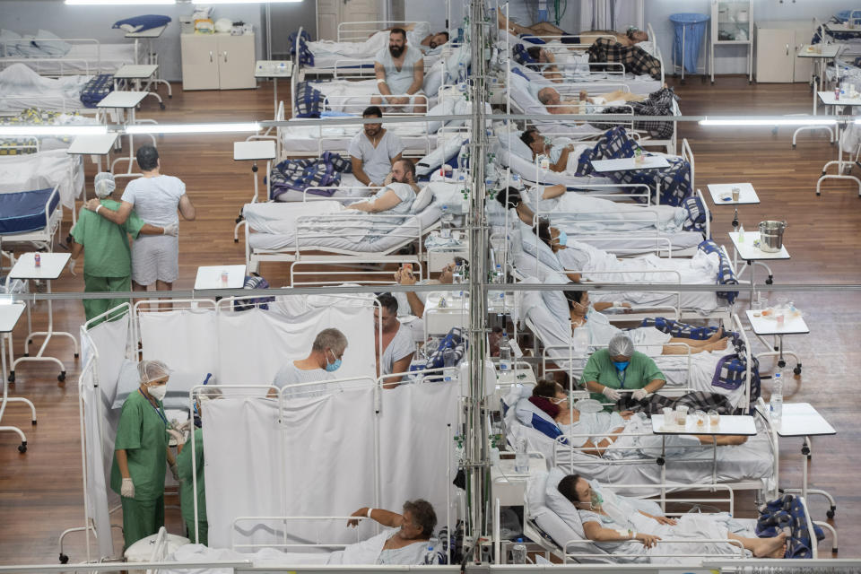 """FILE - COVID-19 patients lie on beds at a field hospital built inside a sports coliseum in Santo Andre, on the outskirts of Sao Paulo, Brazil, on March 4, 2021. As hopes rise that the pandemic is ebbing in the United States and Europe, visions of a second """"Roaring Twenties"""" to match last century's post-pandemic decade have proliferated. (AP Photo/Andre Penner, File)"""