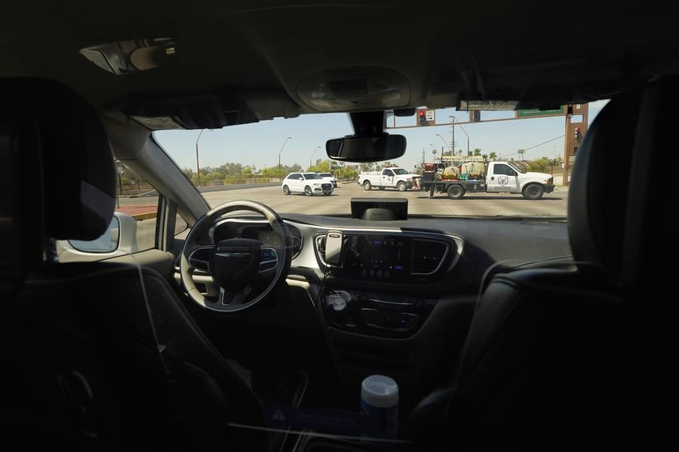 A Waymo minivan moves along a city street as an empty driver's seat and a moving steering wheel drive passengers during an autonomous vehicle ride, Wednesday, April 7, 2021, in Chandler, Ariz. Waymo, a unit of Google parent Alphabet Inc., is one of several companies testing driverless vehicles in the U.S. But it's the first offering lifts to the public with no humans at the wheel who can take over in sticky situations. (AP Photo/Ross D. Franklin)