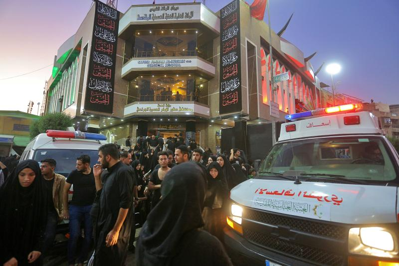 People gather outside a hospital while ambulances bring injured people after a walkway collapsed and set off a stampede as thousands of Shiite Muslims marked one of the most solemn holy days of the year in the holy city of Karbala, Iraq, Tuesday, Sept. 10, 2019. Officials say at least 31 people have died and around 100 others were injured in the chaos Tuesday, which occurred toward the end of the Ashoura procession, causing panic and a stampede, according to two officials. (AP Photo/Anmar Khalil)