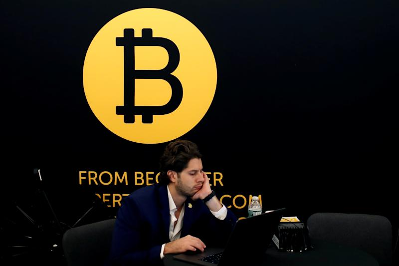 A man works on a laptop beneath the Bitcoin logo at the Consensus 2018 blockchain technology conference in New York City, New York, U.S., May 16, 2018. REUTERS/Mike Segar
