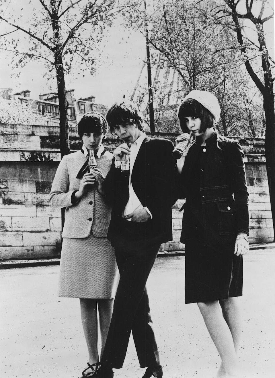 <p>Mick Jagger poses with two models drinking soda pop while in Paris, 1966. </p>