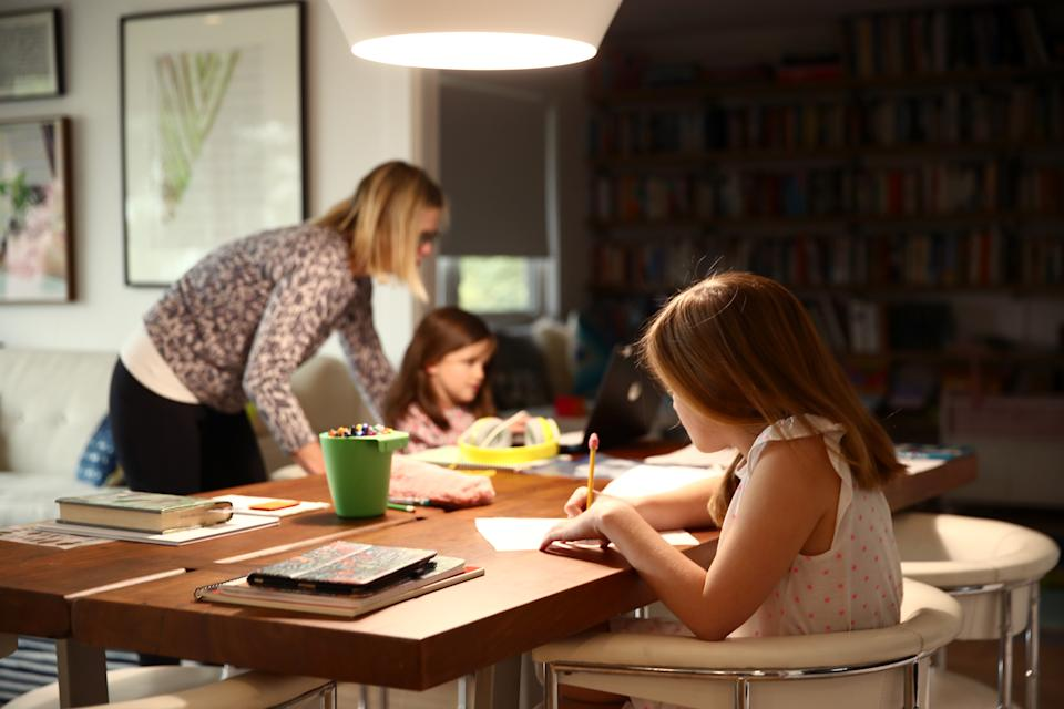 Fourth grader Lucy Kramer (foreground) does schoolwork at her home, as her mother, Daisley, helps her younger sister Meg, who is in kindergarten, on March 18, 2020 in San Anselmo, California. (Photo by Ezra Shaw/Getty Images)