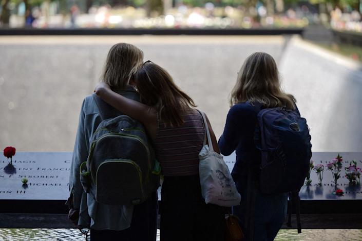 Three people stand together at the National September 11 Memorial & Museum