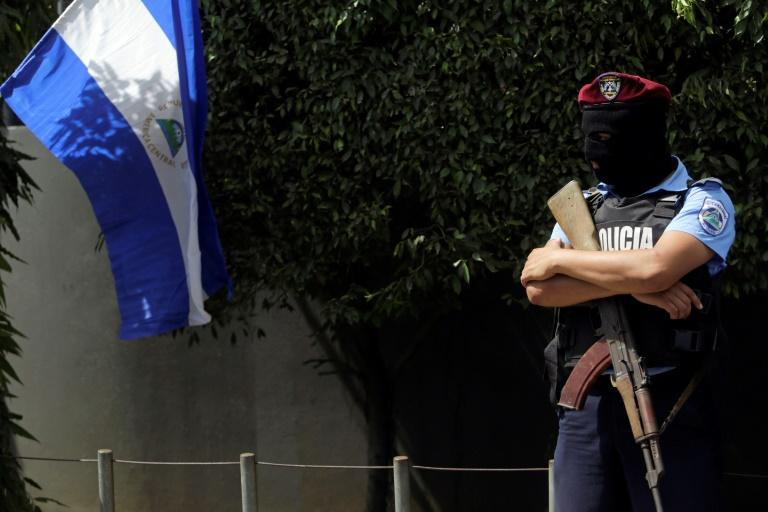 Police officer with face covered stands guard outside the National Judicial Complex building in Managua