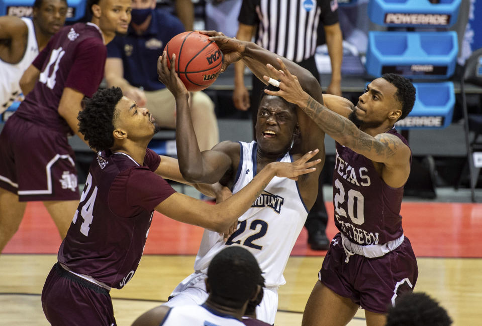 Mount St. Mary's forward Nana Opoku (22) shoots while being defended by Texas Southern forward John Walker III, left, and guard Michael Weathers (20) during the second half of a First Four game in the NCAA men's college basketball tournament Thursday, March 18, 2021, in Bloomington, Ind. (AP Photo/Doug McSchooler)
