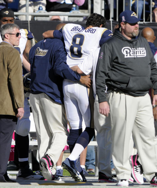 In this Oct. 20, 2013 photo, St. Louis Rams' Sam Bradford (8) is helped from the sidelines after being injured in the second half of an NFL football game against the Carolina Panthers in Charlotte, N.C. Bradford will miss the rest of the season because of a torn knee ligament. The Rams said Monday, Oct. 21, 2013, the extent of the injury to Bradford's left knee was confirmed after an MRI exam. Bradford tore his anterior cruciate ligament in the fourth quarter of Sunday's 30-15 loss to the Panthers when he landed on his knee after being shoved out of bounds by Panthers safety Mike Mitchell. (AP Photo/Mike McCarn)