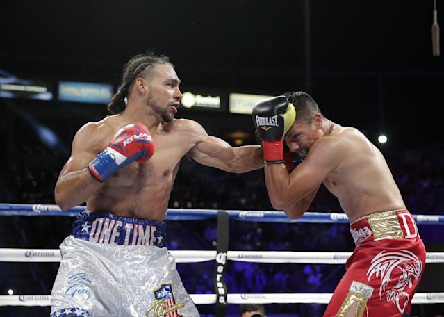 Julio Diaz, right, takes a punch from Keith Thurman during the third round of a WBA interim welterweight title boxing match on Saturday, April 26, 2014, in Carson, Calif. Thurman won by TKO after the third round. Diaz wasn't able to come out for the fourth round due to his rib injury.(AP Photo/Jae C. Hong)