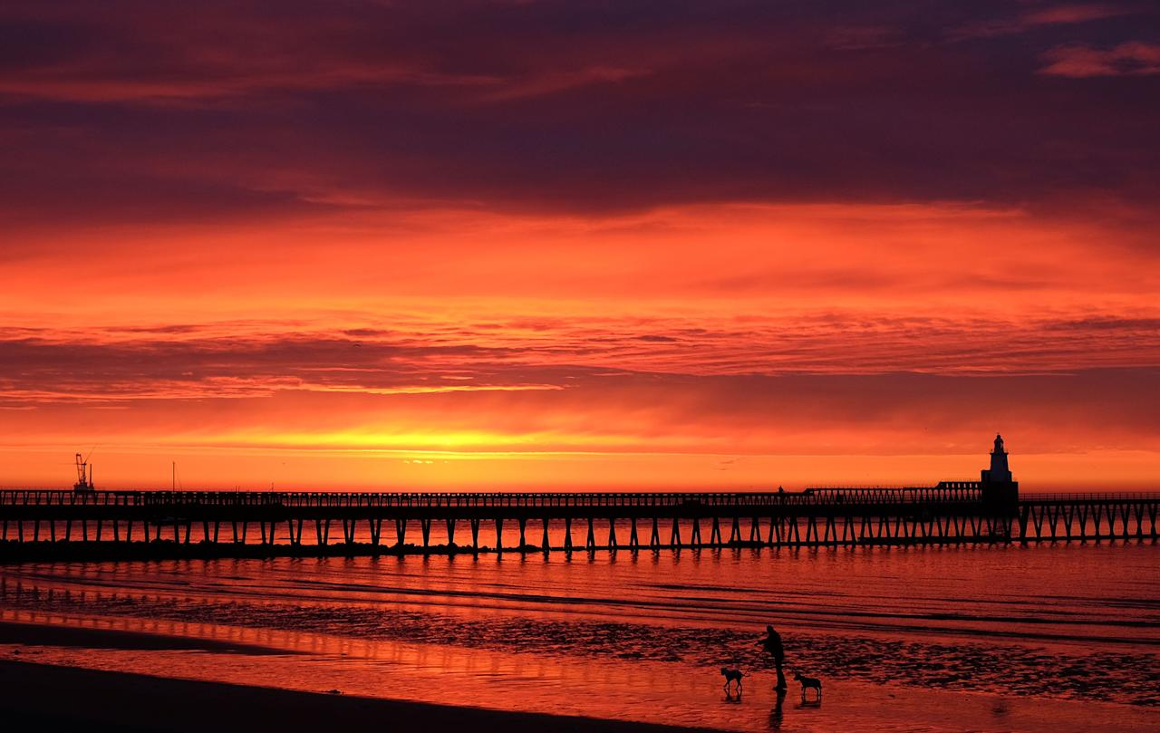 <p>The fire-like sky at dawn over the port of Blyth on the Northumberland coast. (PA) </p>