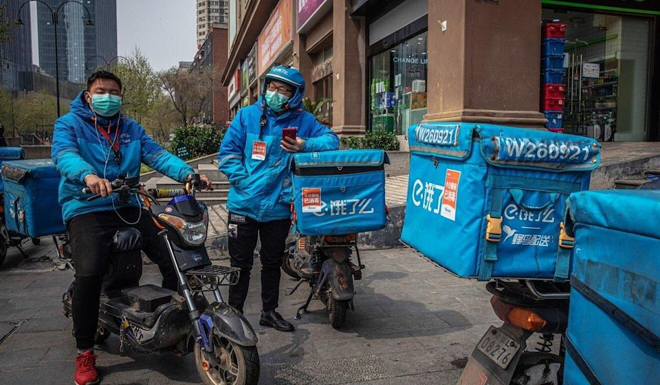 Delivery men rest on their scooters in Wuhan, capital of central China's Hubei province. Photo: EPA-EFE