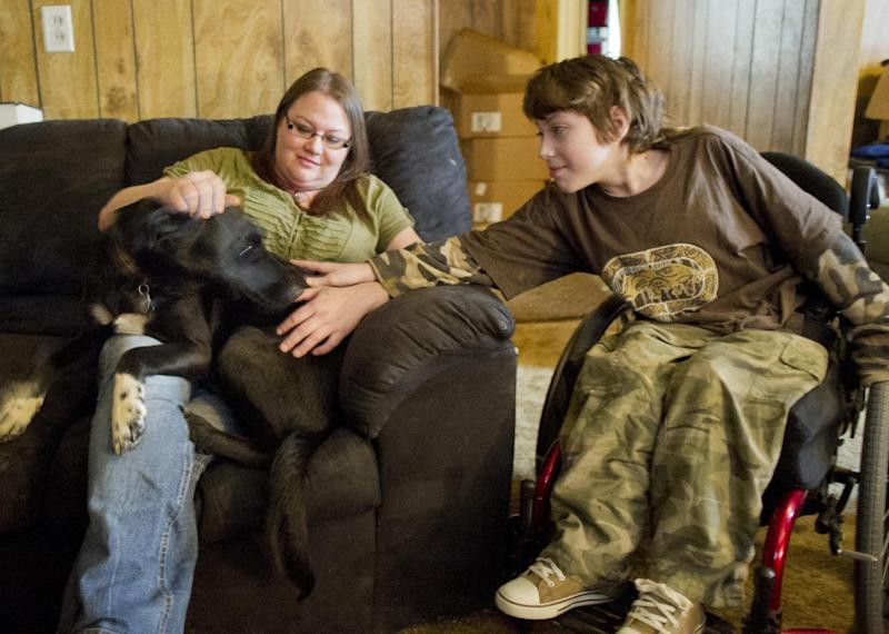 Lori Latch, left, with her son Eric Latch, right, in their home in North Little Rock, Ark., Tuesday, Feb. 4, 2014. Lori Latch, 35, said she was looking forward to having health insurance for the first time since she was a teenager. She and her husband, who is self-employed, have racked up more than $5,000 in bills for emergency room visits. Arkansas' plan for expanding Medicaid by buying private insurance policies for the poor instead of adding them to the rolls was heralded as a model for convincing more Republican-leaning states to adopt a key part of President Barack Obama's health care overhaul. But less than a year after its approval, the program that has extended health insurance to 83,000 people is on the brink of being abandoned. (AP Photo/Brian Chilson) (AP Photo/Brian Chilson)