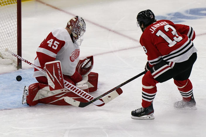 Detroit Red Wings goalie Jonathan Bernier, left, cannot make the save on a goal by Chicago Blackhawks center Mattias Janmark during the third period of an NHL hockey game in Chicago, Saturday, Feb. 27, 2021. (AP Photo/Nam Y. Huh)