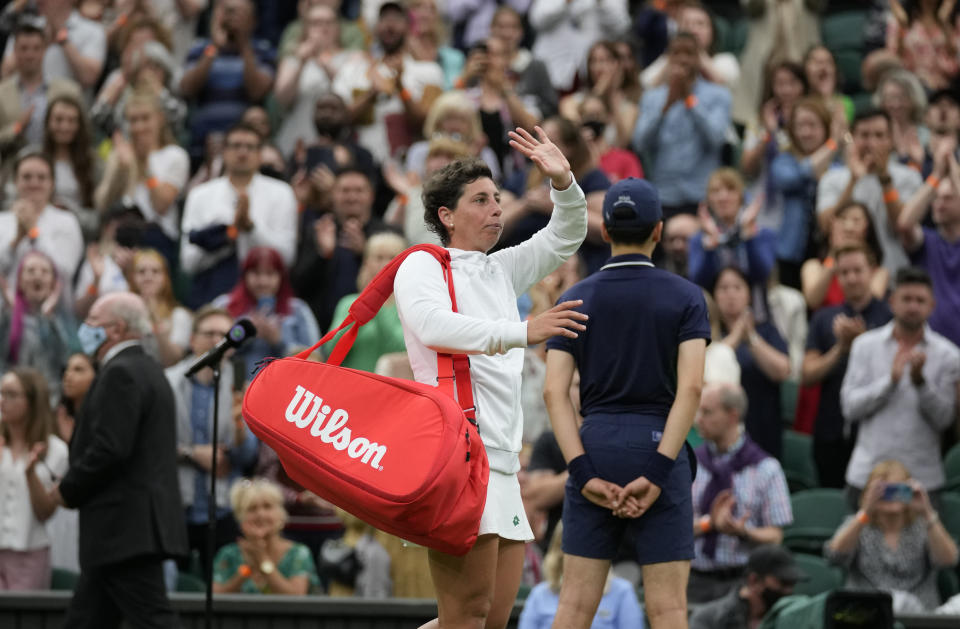 Spain's Carla Suarez Navarro leaves the court after being defeated by Australia's Ashleigh Barty in the women's singles first round match against on day two of the Wimbledon Tennis Championships in London, Tuesday June 29, 2021. (AP Photo/Kirsty Wigglesworth)