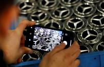 FILE PHOTO: Hubcaps with the logo of German car manufacturer Mercedes Benz sit in a box prior to their installation at the A-class production line at the Daimler factory in Rastatt
