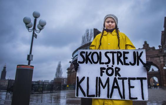 Swedish girl Greta Thunberg holds a placard reading 'School strike for the climate' during a protest against climate change outside the Swedish parliament on 30 November 2018. (Getty Images)