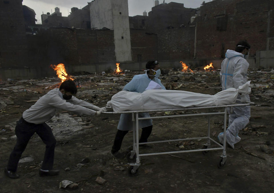 In this May 6, 2021, file photo, the body of a COVID-19 victim is wheeled in for cremation in a ground that has been converted into a crematorium in New Delhi, India.