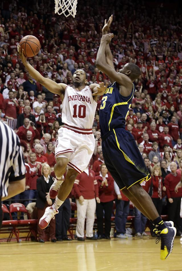 Indiana guard Evan Gordon (10) holds off Michigan guard Caris LeVert while shooting in the second half of an NCAA college basketball game in Bloomington, Ind., Sunday, Feb. 2, 2014. Indiana defeated Michigan 63-52. (AP Photo/Michael Conroy)