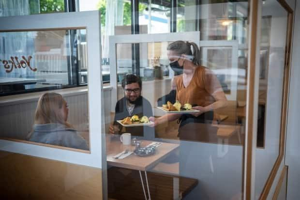 Diners are pictured eating at Yolks restaurant in Vancouver on May 25, the first day indoor dining was allowed after B.C.'s COVID-19 'circuit breaker' measures began in March. (Ben Nelms/CBC - image credit)