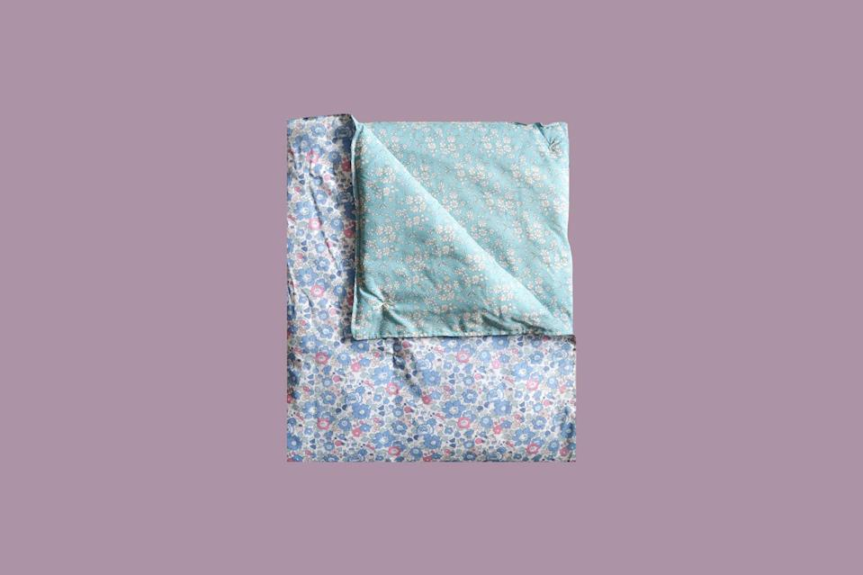 """<p>This vintage-inspired quilt is made with hand-embroidered stitching and the iconic Liberty fabric, one of of our favorites. In the package, it will provide cushioning when it's folded over the gifts. And once opened, it's the perfect thickness to keep the little one dreaming comfortably or for using as a play mat.</p> <p><strong><em>Shop Now:</em></strong><em> Coco & Wolf Liberty Fabric Heirloom Quilt, in Betsy Blue, Rose Quartz, & Capel Turquoise, $145, <a href=""""https://www.thetot.com/product/coco-wolf-liberty-fabric-heirloom-quilt-betsy-blue-rose-quartz-capel-turquoise/"""" rel=""""nofollow noopener"""" target=""""_blank"""" data-ylk=""""slk:thetot.com"""" class=""""link rapid-noclick-resp"""">thetot.com</a></em><em>.</em></p>"""