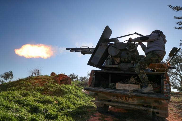 A Turkey-backed Syrian fighter fires a truck-mounted gun in Idlib province in northwestern Syria