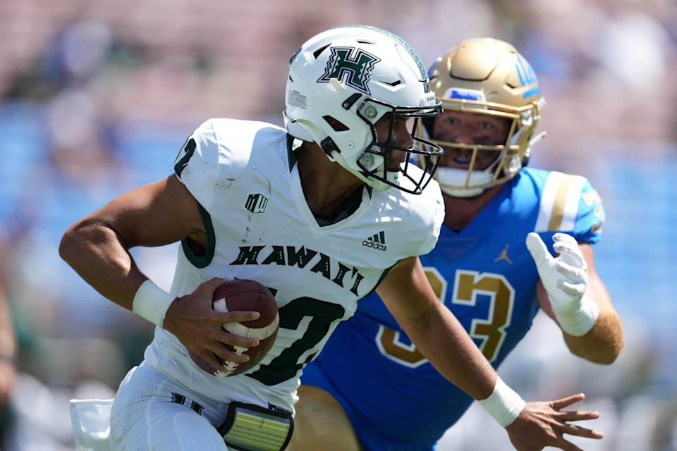 Chevan Cordeiro is pressured by Bo Calvert in the first half at the Rose Bowl. UCLA beat Hawaii 44-10.