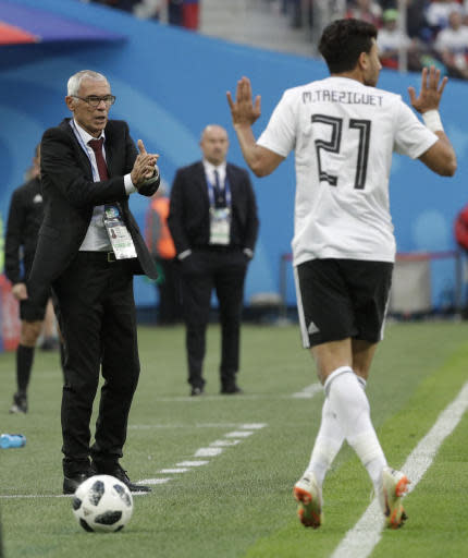 Egypt head coach Hector Cuper, left, clap hands towards Egypt's Trezeguet, right, during the group A match between Russia and Egypt at the 2018 soccer World Cup in the St. Petersburg stadium in St. Petersburg, Russia, Tuesday, June 19, 2018. (AP Photo/Gregorio Borgia)