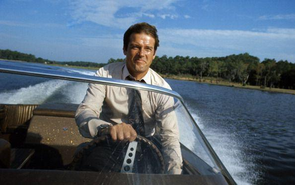 <p>Roger Moore poses driving a speedboat in Kingston, Jamaica during the filming of 'Live And Let Die', 1973.</p>