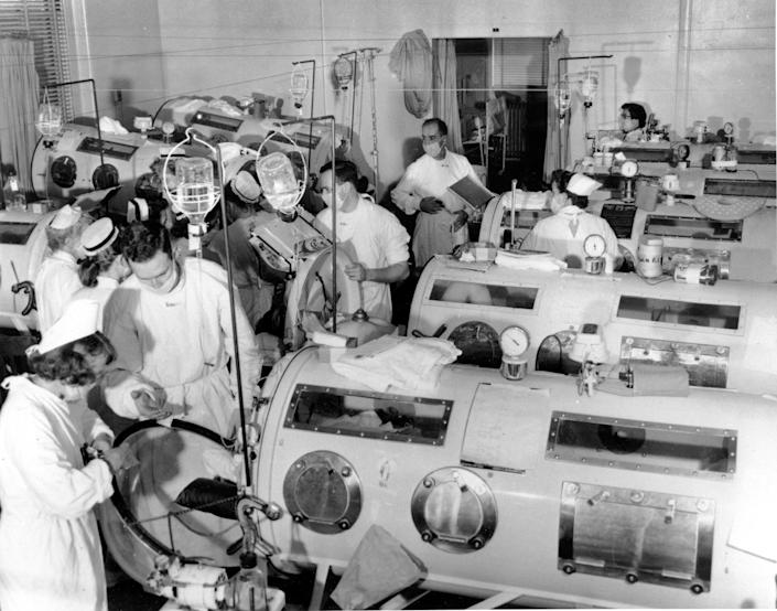 This is a scene in the emergency polio ward at Haynes Memorial Hospital in Boston in 1955, showing critical victims lined up in Iron Lung respirators. The coffin-like devices helped those whose bodies were crippled by polio breathe artificially. Later in 1955, Jonas Salk discovered the vaccine for polio, which today has been eradicated from all but three countries.